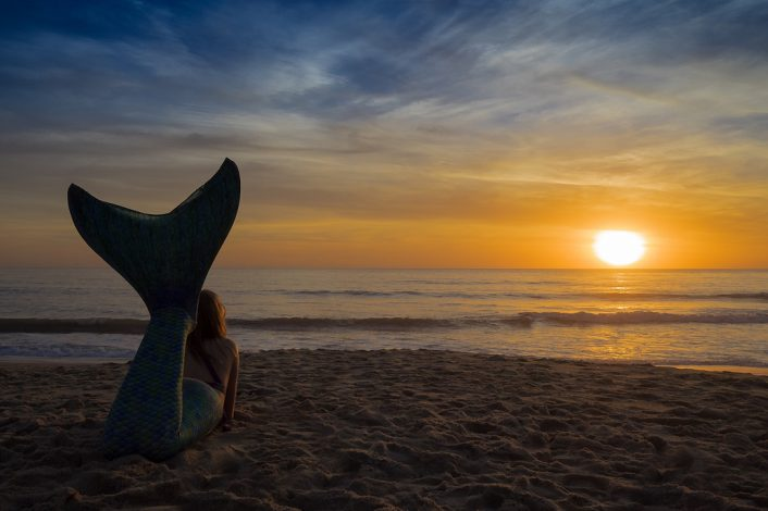 A mermaid takes in a summer sunset before heading back into the sea.
