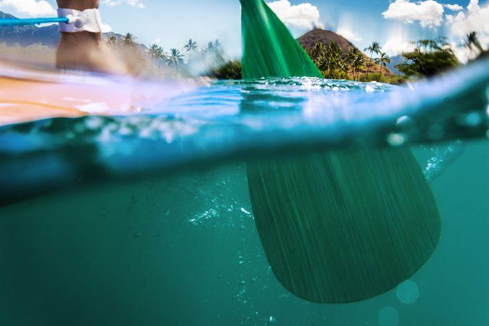 Paddling oar halfway submerged in ocean paddling across ocean surface